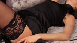 Girl in black erotic lingerie lies down on the bed Footage
