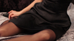 Girl in black dress on bed in the evening Footage