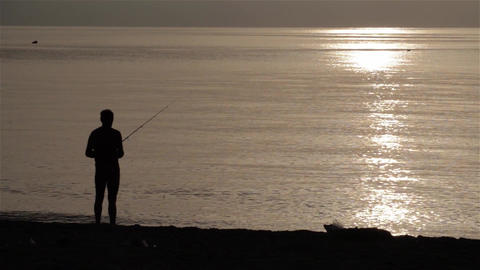 Silhouette of a fisherman on the sea shore while throwing rod after fish 1 Footage