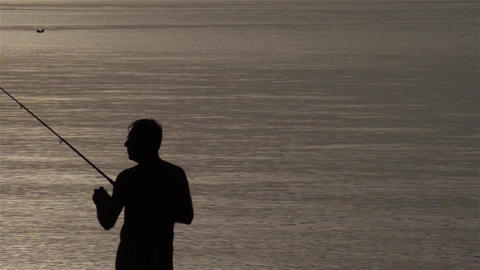 Silhouette of a fisherman on the sea shore while throwing rod after fish 4 Footage