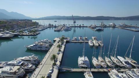 Flying above Porto Montenegro luxury marina pier with white yachts, sailing boat Footage