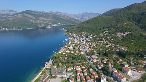 Flying above Montenegro suburb coast line with buildings, cottages, big mountain Footage