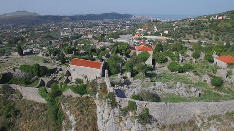 Flying high over old historical fortress ruins and ancient village towards valle Archivo