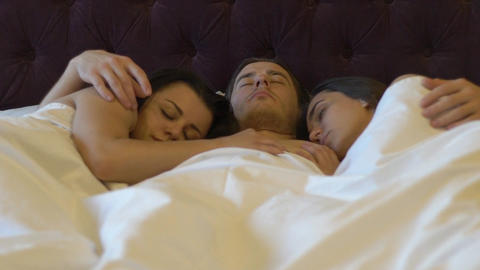 Young Guy Sleeping In Bed Embracing Two Women Live Action