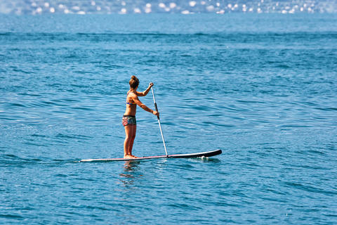 Girl standing on standup paddle surfing in Geneva Lake Montreux 相片