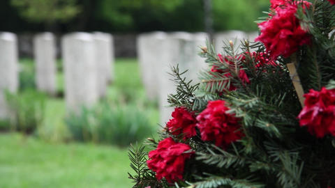Crown of fir branches with red carnations in memory of the dead. Cross of men, h Footage