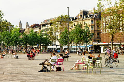 People sitting on chairs on Sechselautenplatz in Zurich 相片
