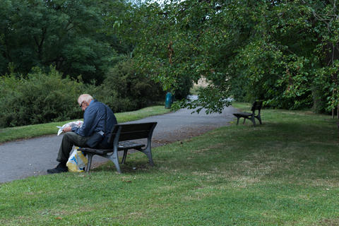 Senior sitting on a park bench reading a newspapers フォト