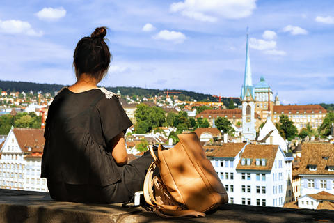Girl sitting on Lindenhof hill and looking into Zurich 相片
