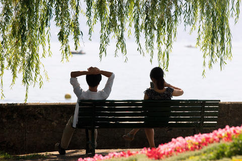 Young couple sitting on bench at Ouchy Lausanne フォト