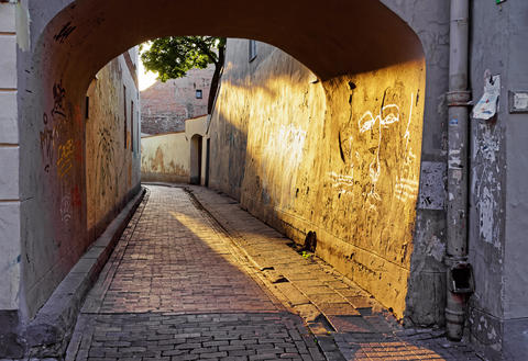 Arch and romantic sunset of old town of Vilnius フォト