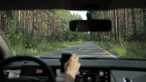 Woman driving empty country road through forest Footage