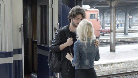 Sad young man in love caressing and saying goodbye to his girlfriend in railway  Footage
