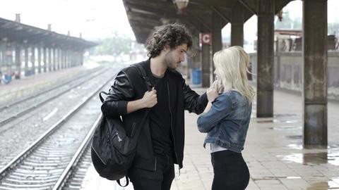 Sad teenage couple saying goodbye on train station platform Footage
