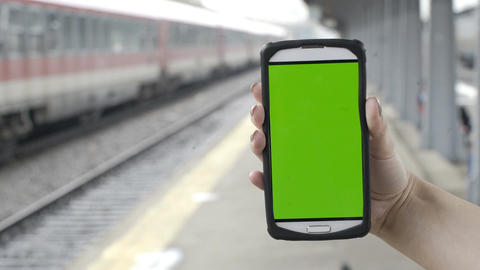 Closeup of woman hands holding smartphone with green screen chroma key in train  Live Action
