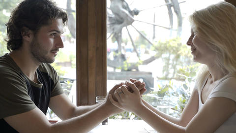 Handsome man sitting at cafe table kissing his girlfriend hand and touching her  Footage