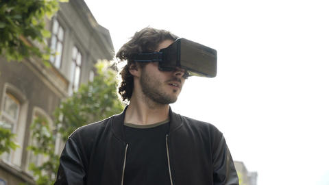 Man having fun with virtual reality glasses outdoor in the city surprised by new Footage