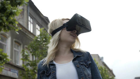 Happy young woman trying a virtual reality vr set feeling amazed Footage