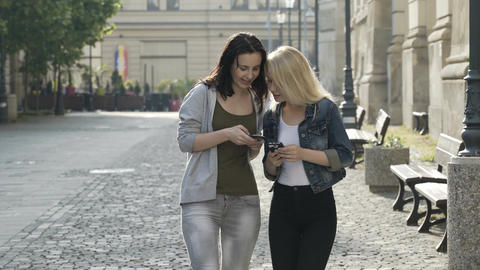 Two beautiful girls hanging out having a conversation and using smartphones whil Footage
