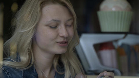 Closeup of happy blonde teenager girl eating ice cream at restaurant enjoying he Footage