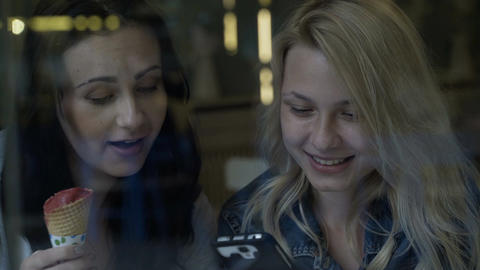 Joyful young women laughing over news in social media feed using smartphone hold Footage