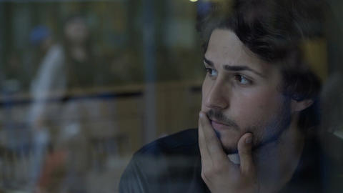 Closeup of stressed business man thinking and sitting near glass window into a p Footage