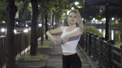 Young blonde girl dancing ballet on street at night expressing grace and eleganc Footage