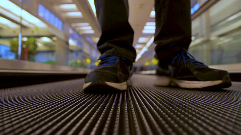 Closeup front view on man legs traveler using moving flat escalator at airport t Footage