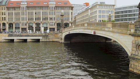 People on the street near the Friedrichsbrucke bridge and the Spree river in rai 画像
