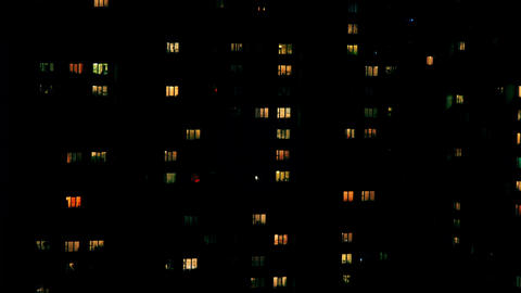 Windows of city building illuminated at night. Timelapse Animation