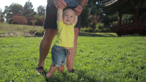 Cute infant taking first steps with father's help Footage