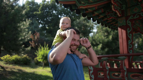Father carrying cute baby boy on shoulders in park Footage