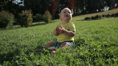 Adorable toddler baby boy clapping hands outdoors Footage