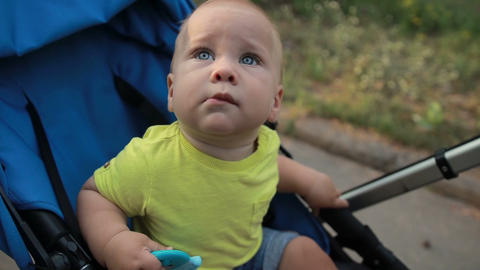 Curious infant boy sitting in pram outdoors Footage