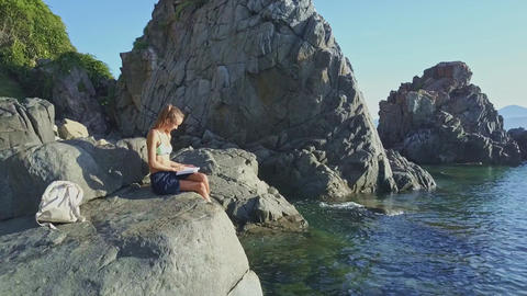 Flycam Moves around Girl Reading Book on Stone near Ocean Footage