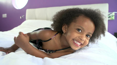 Cute Little Girl Lying On Tummy In Parent's Bed Footage