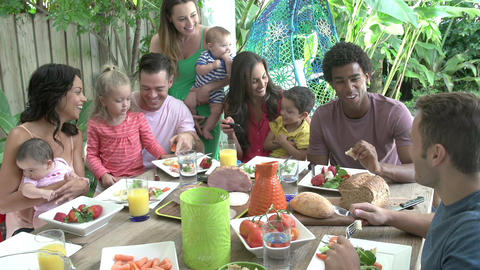 Group Of Families Enjoying Outdoor Meal At Home Footage