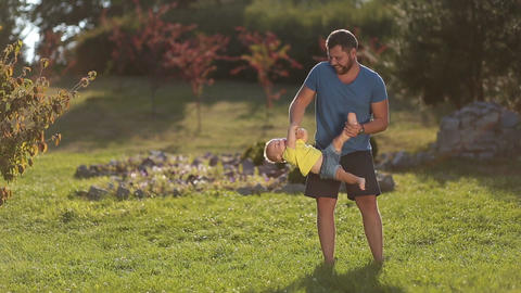 Cheerful father swinging his baby boy in park Footage