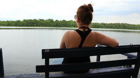 Lonely girl sitting on a bench by the lake and looking away - from behaind Footage