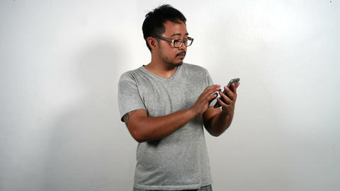 Casual man using smartphone Browsing and Text Messaging ビデオ
