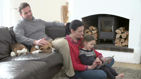 Family Relaxing Watching Television And Using Digital Tablet Footage