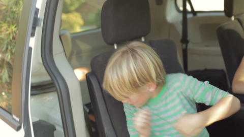 Mother Making Sure Children Are Safe In Back Seat Of Car Live Action