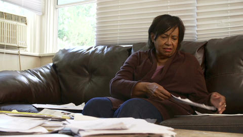 Worried Senior Woman Sitting On Sofa Looking At Bills Footage