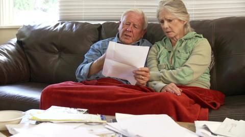 Worried Senior Couple Sitting On Sofa Looking At Bills Footage
