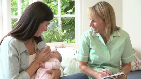 Mother With Baby Meeting With Health Visitor At Home Footage