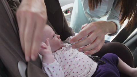 Mother Putting Baby Daughter In Safety Seat On Car Journey Live Action