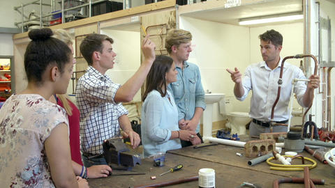 Teacher Helping College Students Studying Plumbing Live Action