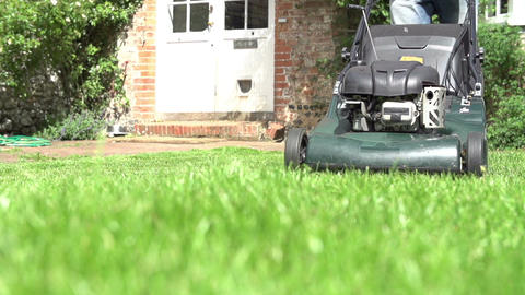Slow Motion Sequence Of Man Cutting Lawn With Mower Live Action