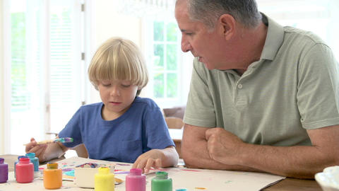 Grandfather Painting Picture With Grandson At Home Footage