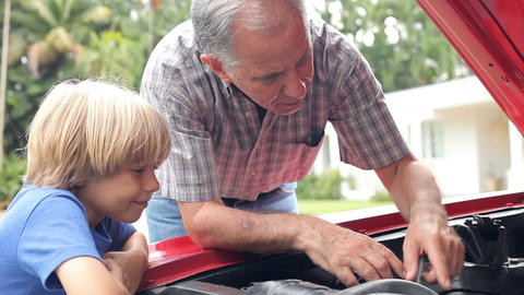Grandfather And Grandson Working On Restored Classic Car Footage